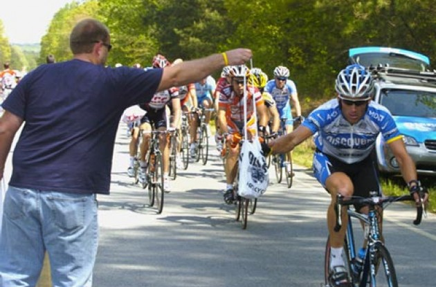 Lance Armstrong grabs a musette bag. Photo copyright Casey Gibson.