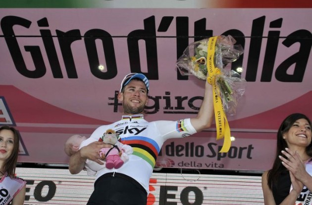 Mark Cavendish celebrates his stage win on the podium with his newborn child and the podium trophys.