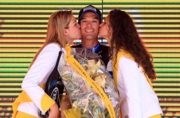 David Millar celebrates his powerful stage win on the podium with the podium girls. Photo Fotoreporter Sirotti.