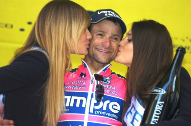 A happy Michele Scarponi on the podium with a flirting podium girl. Photo copyright Fotoreporter Sirotti.